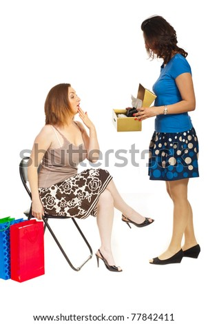 Clerk showing new shoes to a customer woman with surprised face  over white background