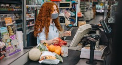 Clerk woman with face mask in a supermarket working at checkout counter. Female cashier scanning grocery items for customer during pandemic.