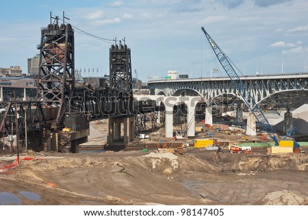 CLEVELAND, OH - MARCH 18: Workers erect a set of columns for the new Innerbelt Bridge on March 18, 2012 in Cleveland, Ohio.  The new bridge will open in 2013 and replace the one seen on the right.