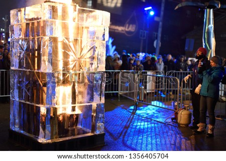 Cleveland, Ohio/USA - February 23 2019: Brite Winter Festival on the Flats under the bridge near downtown. Spectators watch as fire and ice burn begins to engulf the piece. #1356405704