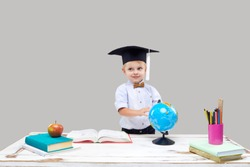 Clever and smart child, prodigy. A little boy in a graduation cap is studying geography on a globe. Getting ready for school lessons. Sitting at a desk with books on a gray isolated background
