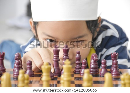 Clever Asian boy concentrated and thinking with chess game challenge #1412805065