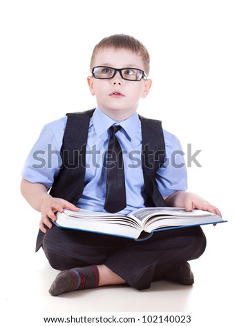 clever boy with a book wearing glasses isolated in studio