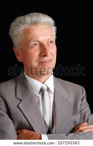 Clever elderly man in suit on black background