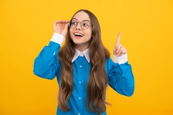 Clever idea. Clever girl in eyeglasses yellow background. School age child with raised finger. Eureka. Basic education.