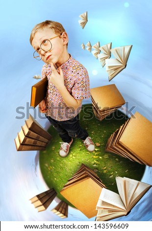 Clever little boy in glasses standing on abstract book planet