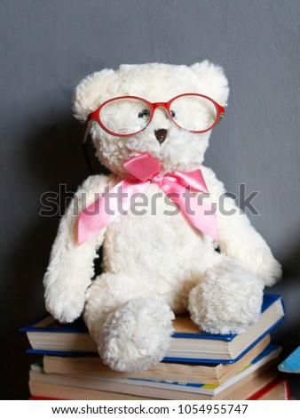 Clever white teddy bear in red glasses