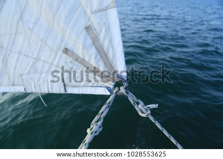 Clew of a genoa sail, sheets tied through a reinforced grommet with bowlines against dark water.