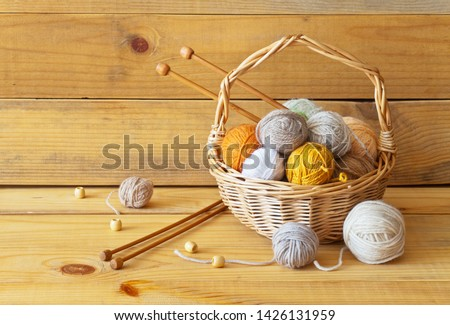 Clews of warm soft wool and mohair yarn lie in a wicker basket with wooden knitting needles. Rustic still life on a wooden background. Concept of needlework, hobbies and knitting. Closeup, copy space