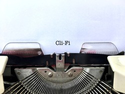 Cli-Fi (Climate Fiction) literature genre heading title typewritten on vintage old fashioned manual typewriter machine on white paper, author writing style concept close up