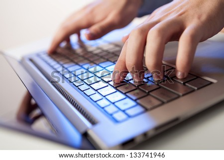 Click! Hands of a man on a keyboard with blue backlighting. #133741946