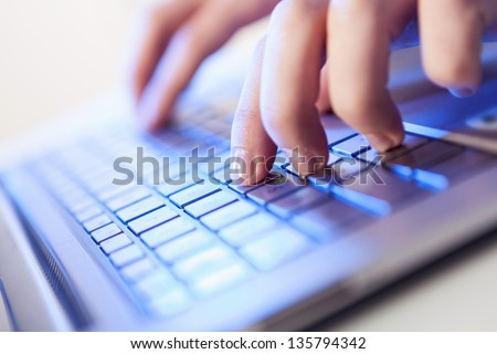 Click! Hands of a man on a keyboard with blue backlighting. #135794342