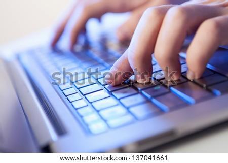 Click! Hands of a man on a keyboard with blue backlighting. #137041661