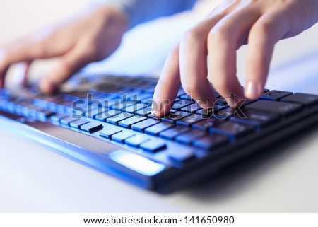 Click! Hands of a man on a keyboard with blue backlighting. #141650980