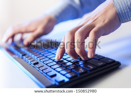 Click! Hands of a man on a keyboard with blue backlighting. #150852980