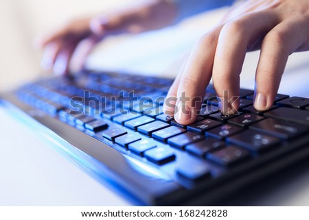 Click! Hands of a man on a keyboard with blue backlighting.