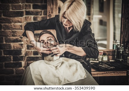 Client during beard shaving in barber shop - Shutterstock ID 353439590