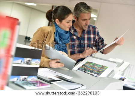 Client in printshop controlling work before final printing
