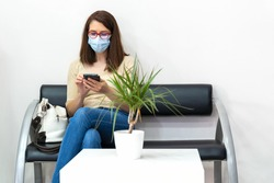 Client in the waiting room with mask and looking at the mobile