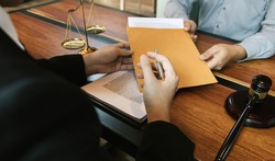 Client is submitting information on the paper of the prosecution document to the lawyer.