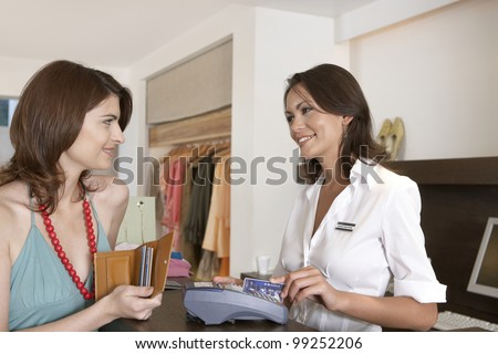 Client making payment at store's till with credit card.