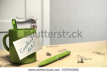 client office with note where it is written contact us onto a mug, there is also paperclips and a pen onto the table, at the background there is a blurry door and a wall