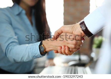 Client shaking hands with insurance agent in office closeup. Business cooperation concept