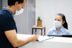 Client Signing Paper At Reception Desk In Face Mask