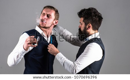 Client with strict face smoke cigar and drink whiskey while tailor working. Man with beard and measuring tape busy. Luxury clothes concept. Tailor measure chest for sewing suit, grey background. #1070696396