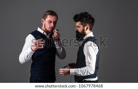 Client with strict face smoke cigar and hold glass with drink while tailor working. Man with beard holds measuring tape. Tailor service concept. Tailor taking measurements for sewing, grey background. #1067978468