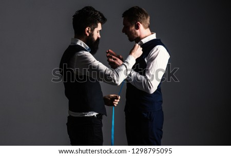 Client with strict face smoke cigar and hold glass with drink while tailor working. Tailor taking measurements for sewing, grey background. Man with beard holds measuring tape. Tailor service concept. #1298795095
