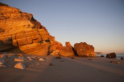 cliff and boulders on the beach fallen from eroded cliff, illuminated by soft sunlight
