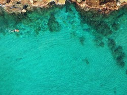 Cliff and rocks on a seashore with a blue water. Top view.