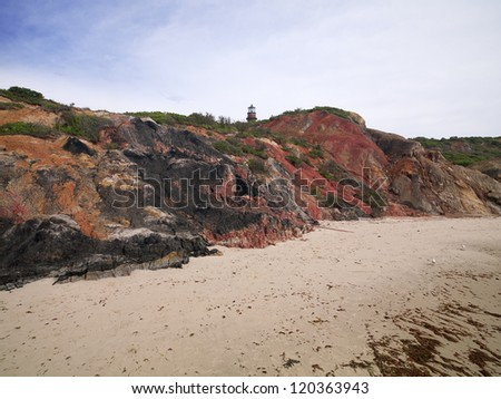 Cliff at beach with watchtower and sky in background.