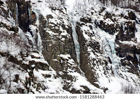 cliff covered with snow and big icicles #1581288463