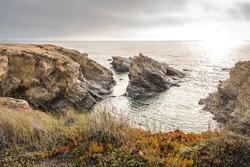 Cliff seascape with carpobrotus edulis, rocks in the sea with brilliant sunlight on the beach of Cerro da Águia, Porto Covo - Vicentine Coast Natural Park PORTUGAL