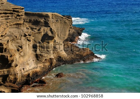 Cliff side of the Green Sand Beach, Big Island of Hawaii, wind and wave erosion is seen in the sand stone cliff face.  Aqua blue water and waves surround cliff.