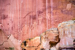 Cliff wall petroglyphs symbols of ancient Anasazi Indian tribe people in Capitol Reef National Park in Utah with red rock color closeup