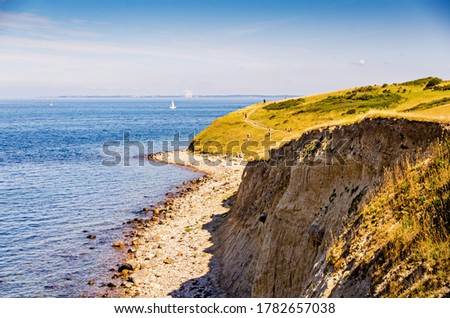 Cliff walls on the beach with hiking trails along the sea. Landscape in Fyns Hoved in Denmark. Stockfoto ©