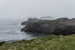 Cliffs and rock formations near Kirkjufjara beach in Iceland on an overcast, foggy day.