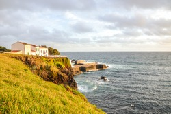Cliffs by the Atlantic ocean in fishermans village Lagoa, Sao Miguel Island, Azores, Portugal. Traditional houses on the hill above the sea. Sunset light. Horizontal photo