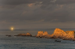 Cliffs with lighthouse beam on twilight, with rocks illuminated by last sun rays before sunset, sunlight Brittany, France