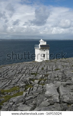 Cliffy coast of the Atlantic Ocean in The Burren, famous natural landmark of Ireland with the lighthouse Blackhead. County Clare, West Coast of Ireland