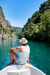 cliffy rocks of Verdon Gorge at lake of Sainte Croix, Provence, France, Provence Alpes Cote d Azur, blue green lake with boats in France Provence. Europe, young men in paddle boat