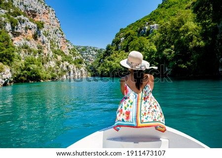 cliffy rocks of Verdon Gorge at lake of Sainte Croix, Provence, France, Provence Alpes Cote d Azur, blue green lake with boats in France Provence. Europe, young woman in peddle boat looking at river Stock photo ©