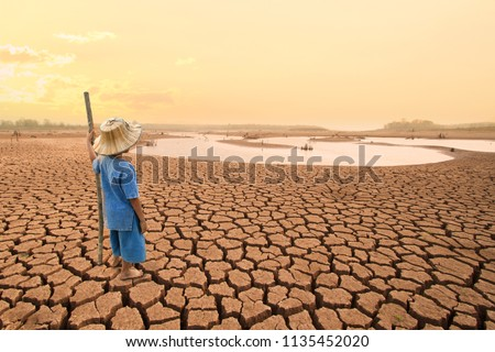 Climate change and World environmental concept. Children looking at drying river after Drought impact on summer.