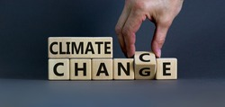 Climate change symbol. Hand flips a cube and changes words 'climate change' to 'climate chance'. Beautiful grey background, copy space. Business and climate change concept.