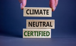 Climate neutral certified symbol. Wooden blocks with words 'Climate neutral certified'. Male hand. Beautiful grey background, copy space. Business and climate neutral certified concept.