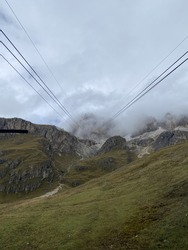 Climb mountain peaks through the clouds  and the fog in the open cabins of the cable car at Passo Pordoi mountain pass, from Terrazza delle Dolomiti Located between Arabba and Canazei Italy, Europe