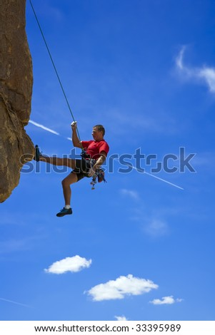 Climber ascends a steep, rock overhang in Joshua Tree National Park, California.